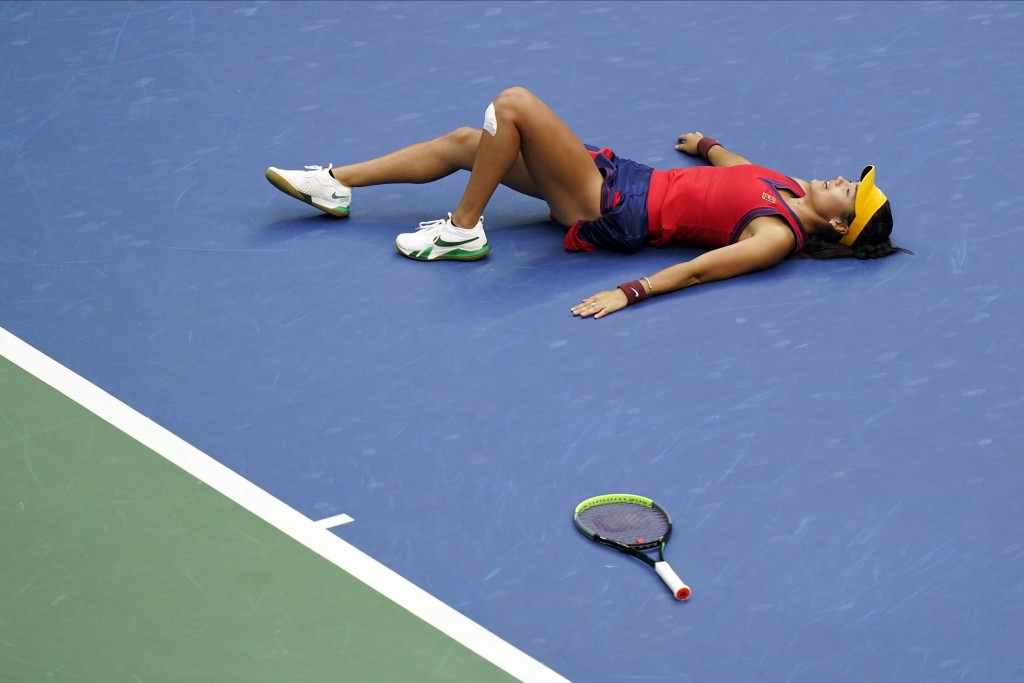 Emma Raducanu, of Britain, lies on the court after defeating Leylah Fernandez, of Canada, during the women's singles final of the US Open tennis champ...