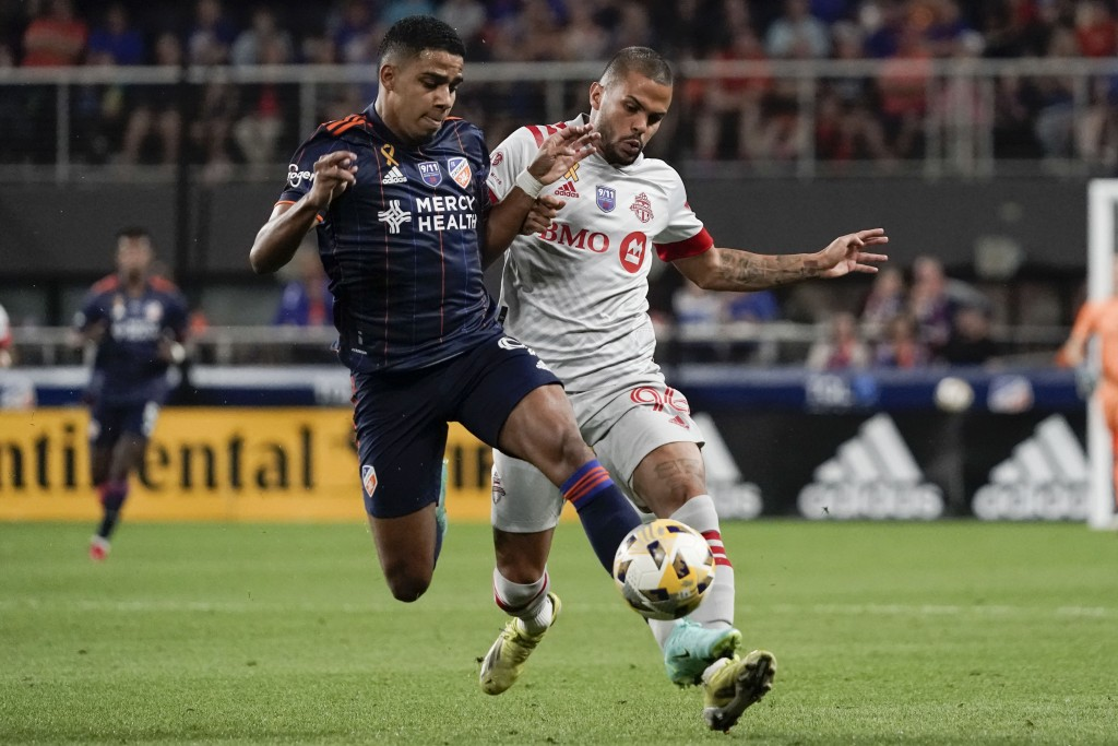 FC Cincinnati forward Brenner, left, and Toronto FC defender Auro fight for the ball during the first half of an MLS soccer match Saturday, Sept. 11, ...