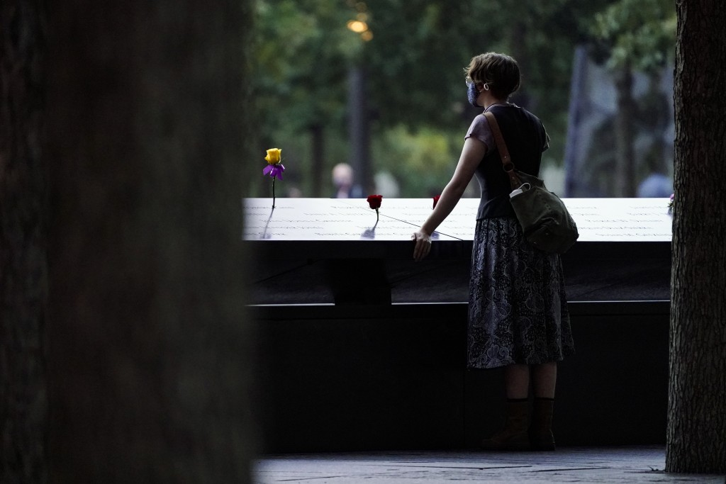 A mourner stands at the south pool before ceremonies to commemorate the 20th anniversary of the Sept. 11 terrorist attacks, Saturday, Sept. 11, 2021, ...