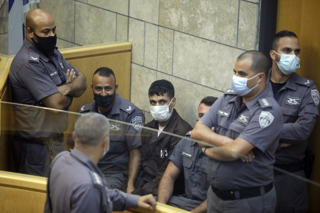 CORRECTS NAME, Mahmoud Aradeh is surrounded by guards as they stand in a courtroom in Nazareth, Israel, after he and three other Palestinian fugitives...