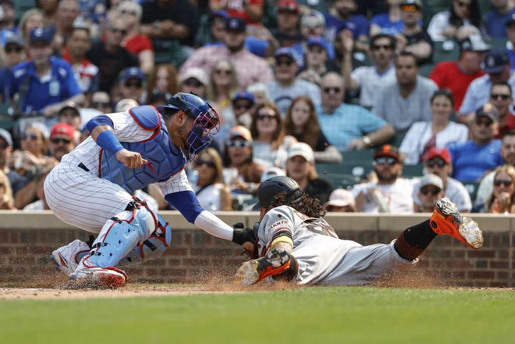 Chicago Cubs catcher Willson Contreras, left, tags out San Francisco Giants' Brandon Crawford, right, at home plate during the third inning of a baseb...