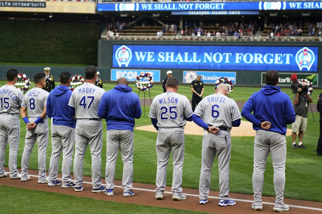A moment of silence is observed by the Kansas City Royals baseball players as wreathes stood behind the mound to mark the 20th anniversary of Sept. 11...