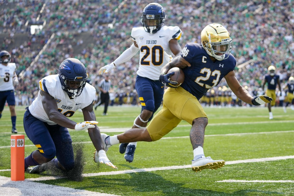 Notre Dame running back Kyren Williams (23) scores a touchdown in front of Toledo's Saeed Holt (20) and Nate Givhan (48) during an NCAA college footba...