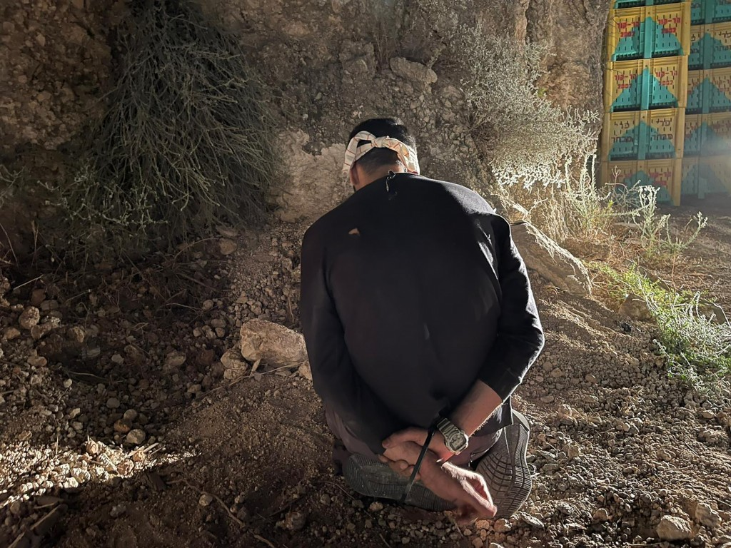 In this photo provided by Israel Police, Mohammed Aradeh, one of the six Palestinian fugitives, is blindfolded and handcuffed after being recaptured i...