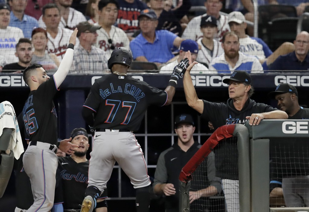 Miami Marlins' Bryan De La Cruz (77) is congratulated upon his return to the dugout after hitting a home run off Atlanta Braves' Richard Rodriguez in ...
