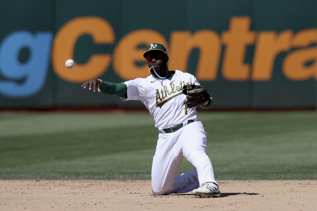 Oakland Athletics' Elvis Andrus (17) throws out Texas Rangers' Nathaniel Lowe from his knees in the sixth inning of a baseball game Saturday, Sept. 11...