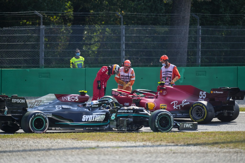 Mercedes driver Valtteri Bottas of Finland, left, drives past Ferrari driver Carlos Sainz of Spain after he crashed during a free practice at the Monz...