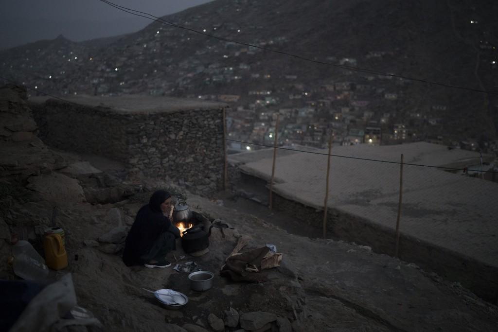 A woman cooks dinner outside her house in Kabul, Afghanistan, Saturday, Sept. 11, 2021. (AP Photo/Felipe Dana)