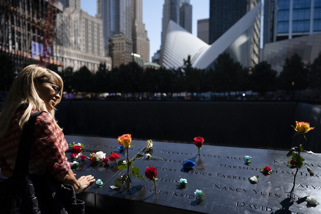 Mourners gather at the north pool adorned with flowers during ceremonies to commemorate the 20th anniversary of the Sept. 11, 2001 terrorist attacks, ...