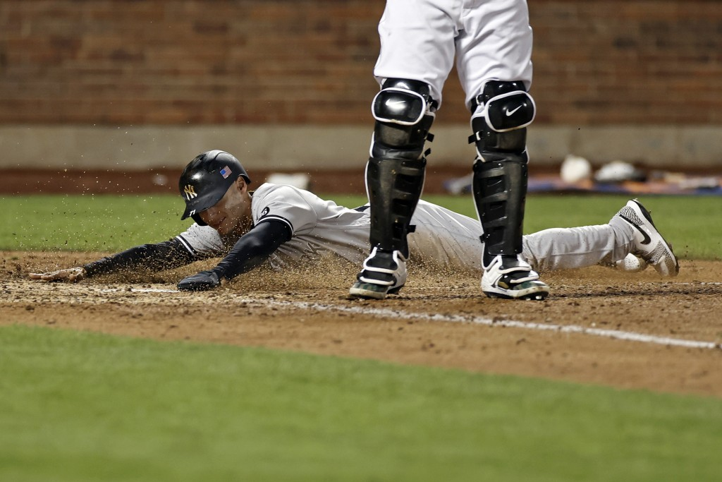 New York Yankees' Andrew Velazquez scores a run behind New York Mets catcher James McCann during the eighth inning of a baseball game on Saturday, Sep...