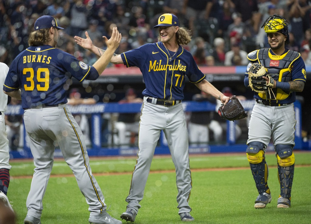 Milwaukee Brewers starting pitcher Corbin Burnes (39) greets relief pitcher Josh Hader as Omar Narvaez watches at the end of a baseball game against t...