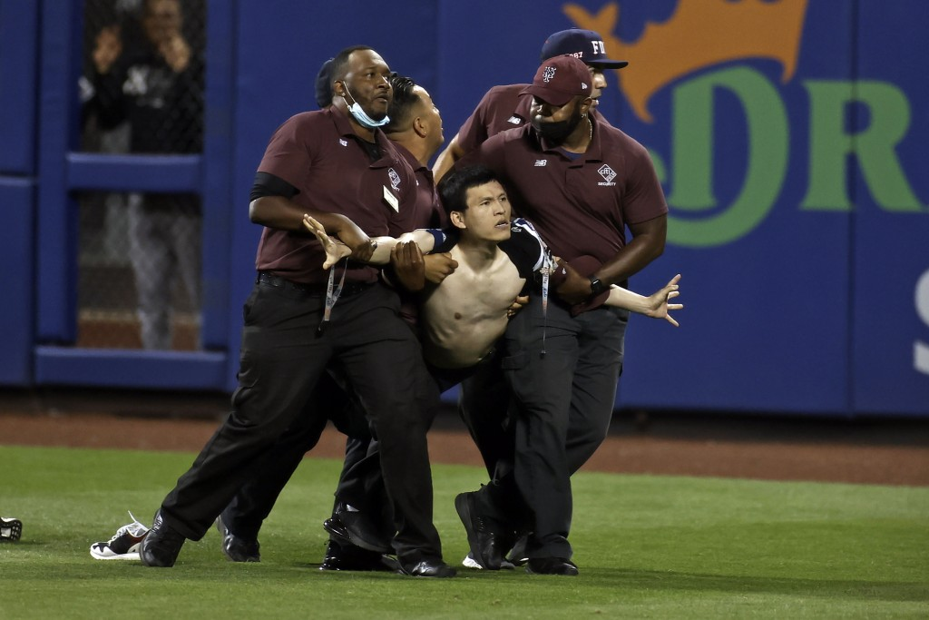 A fan is carried by security guards after running onto the field during the sixth inning of a baseball game between the New York Yankees and the New Y...