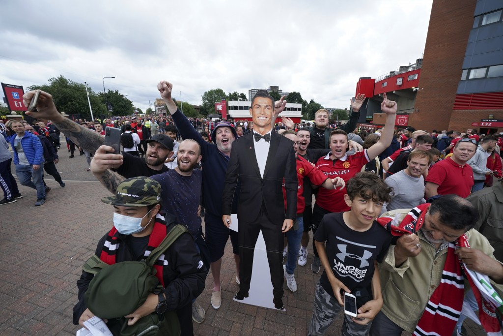 Fans poses for selfies with a cutout of Manchester United's Cristiano Ronaldo before the English Premier League soccer match between Manchester United...