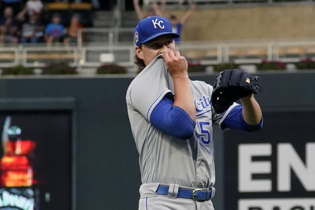 Kansas City Royals pitcher Brady Singer wipes his face after giving up a solo home run to Minnesota Twins' Byron Buxton in the first inning of a baseb...