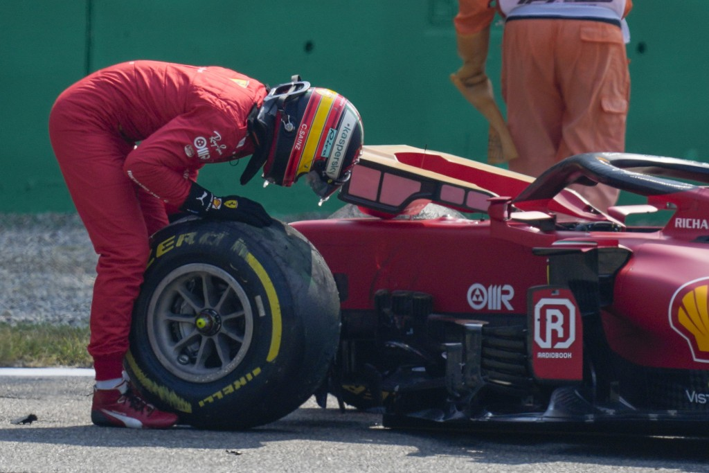 Ferrari driver Carlos Sainz of Spain inspects a tyre of his car after crashing during a free practice at the Monza racetrack, in Monza, Italy , Saturd...