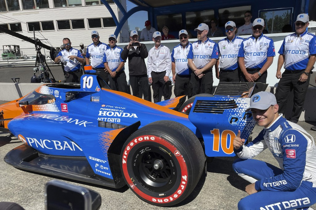 Driver Alex Palou, front right, poses by his car and team after winning the first pole of his career during qualifying for Sunday's IndyCar auto race,...