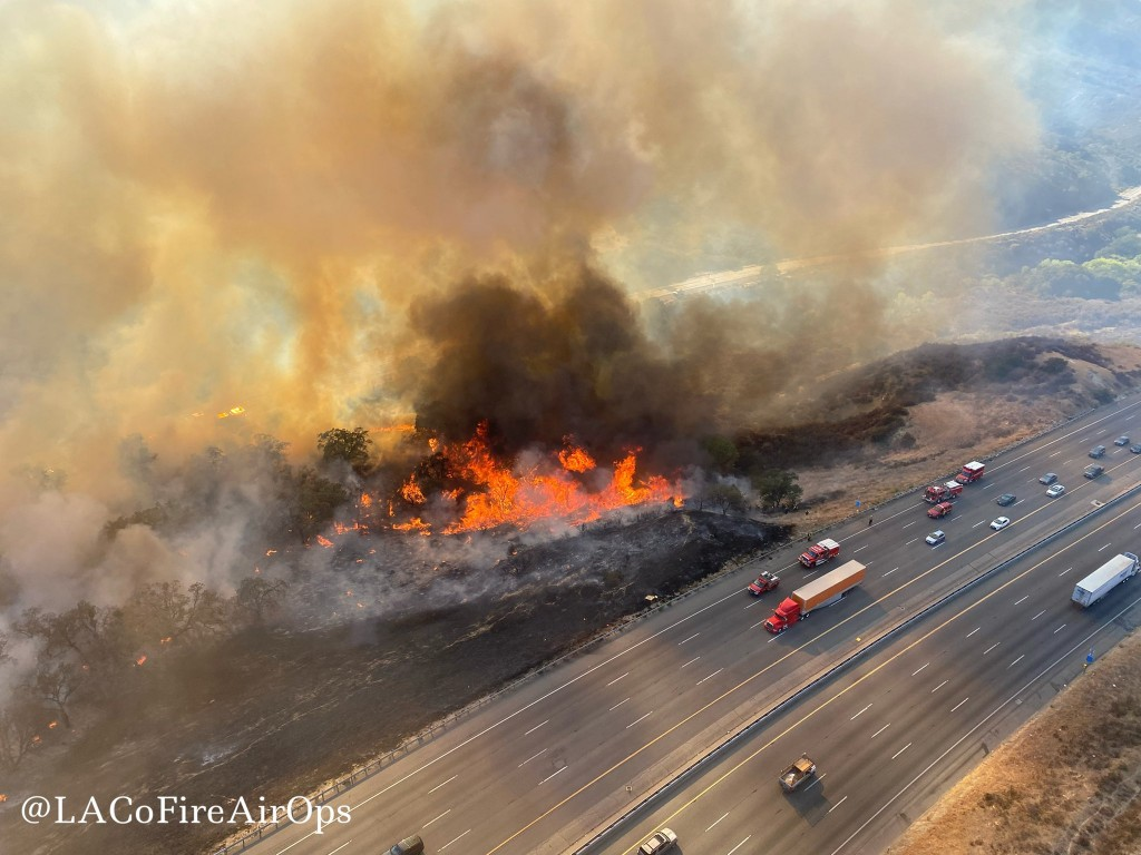 In this aerial photo released by the Los Angeles County Fire Department Air Operations traffic passes the Route fire, a brush wildfire off Interstate ...