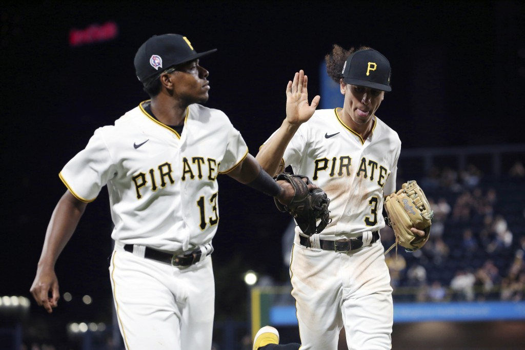 Pittsburgh Pirates third baseman Ke'Bryan Hayes (13) and Pittsburgh Pirates shortstop Cole Tucker (3) high-five in the fifth inning of a baseball game...