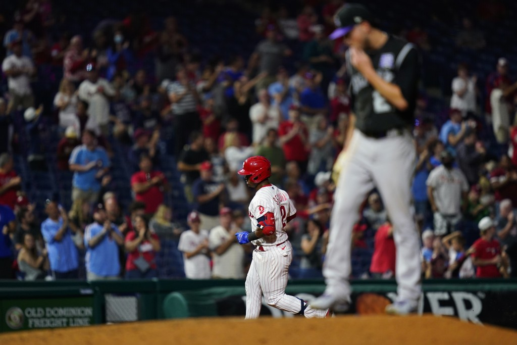 Philadelphia Phillies' Jean Segura, left, rounds the bases past Colorado Rockies pitcher Kyle Freeland after hitting a home run during the fifth innin...