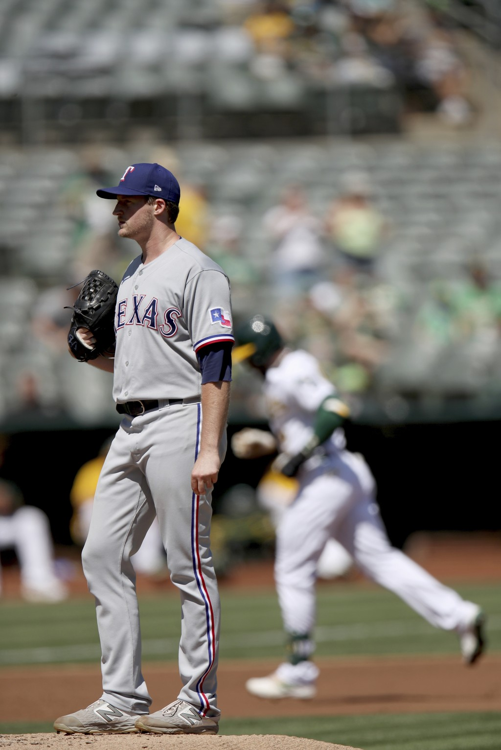 Texas Rangers' starting pitcher Wes Benjamin (63) looks on as Oakland Athletics' Starling Marte (2) rounds the bases after a solo home run in the firs...