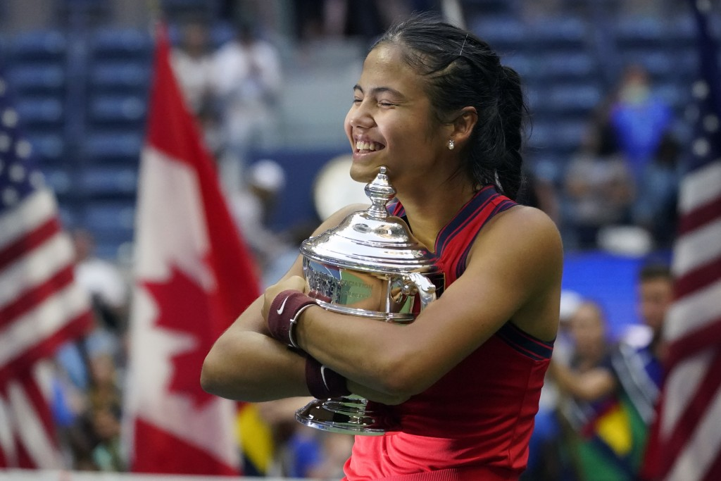 Emma Raducanu, of Britain, hugs the US Open championship trophy after defeating Leylah Fernandez, of Canada, during the women's singles final of the U...