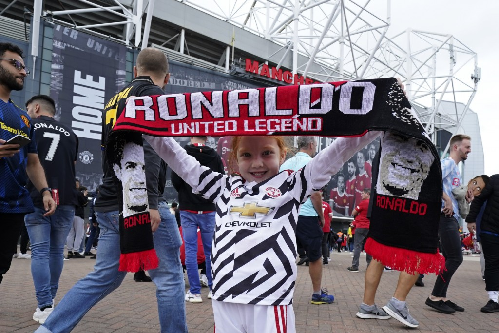 Edie Maisland, 5 years old, holds up a scarf with the name of Manchester United's Cristiano Ronaldo outside the stadium before the English Premier Lea...