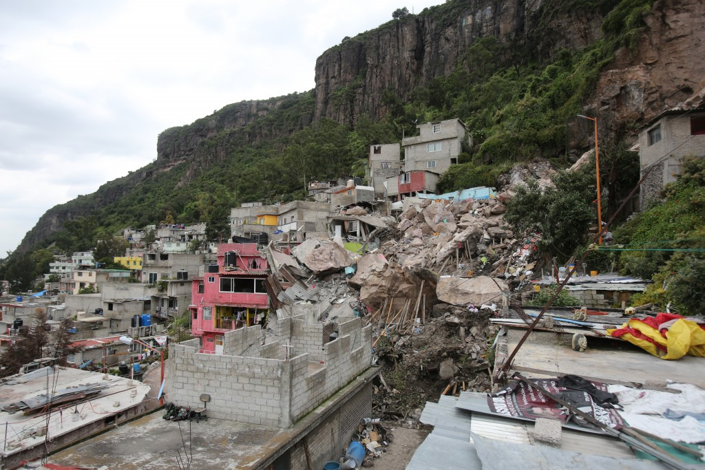 Boulders and debris that plunged from a mountainside rest atop homes in Tlalnepantla, on the outskirts of Mexico City, Saturday, Sept. 11, 2021. A sec...