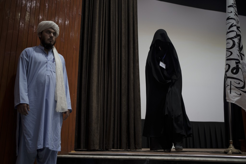 A women walks down from the stage inside an auditorium at Kabul University's education center during a demonstration in support of the Taliban governm...