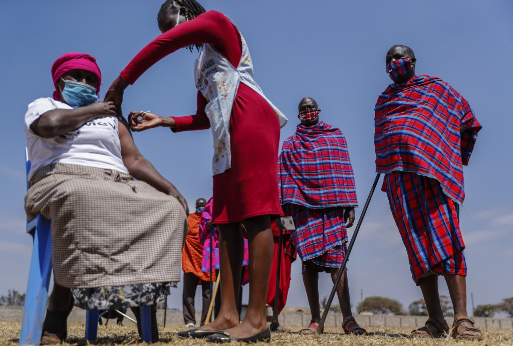 Maasai men queuing to receive the AstraZeneca coronavirus vaccine look over as a woman, who is not, Maasai receives a jab at a clinic in Kimana, south...