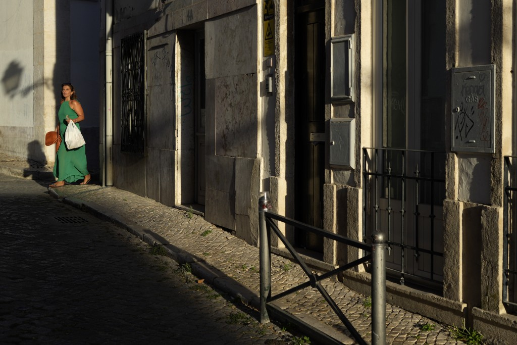 A woman walks across a street as the sun sets in Lisbon, Friday, Sept. 10, 2021. After Sunday people in Portugal' won't be required to wear face masks...