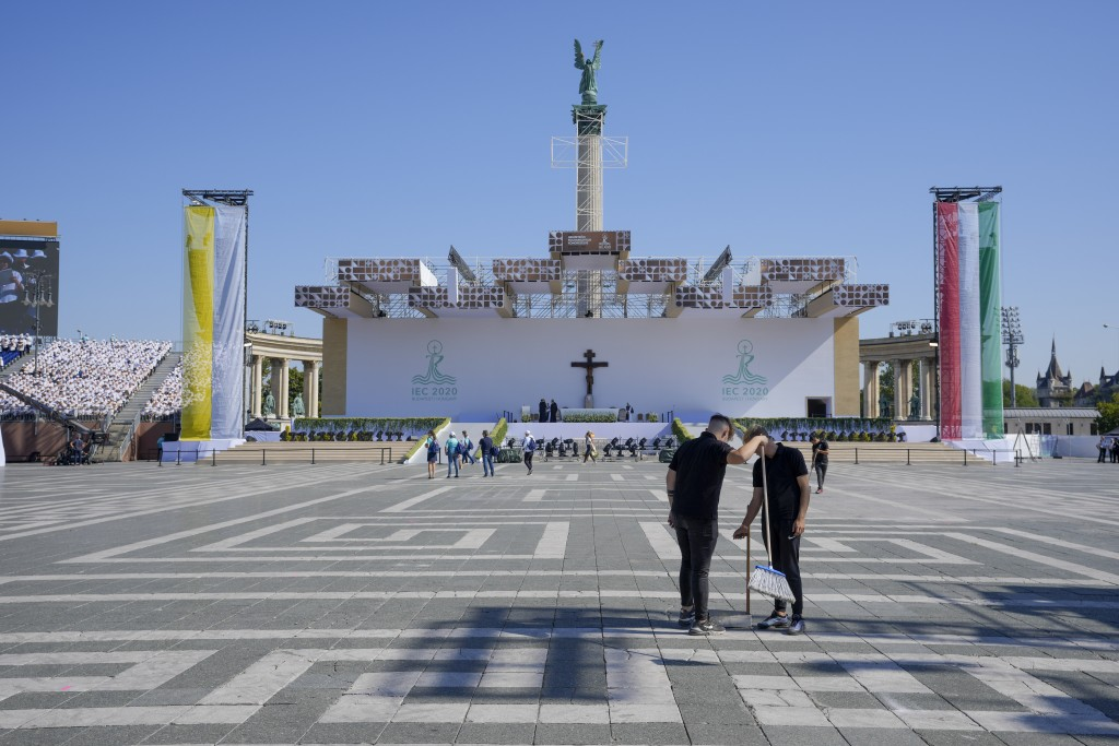 Workers clean the pavement in the fenced off area in Heroes' Square where Pope Francis will be celebrating mass, in Budapest, Hungary, Saturday, Sept....