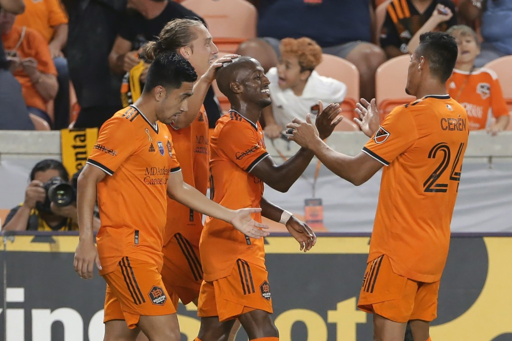 Houston Dynamo's Fafa Picault, center, is surrounded after his second goal of the game by team mates, from left, Memo Rodriguez, Griffin Dorsey and Da...