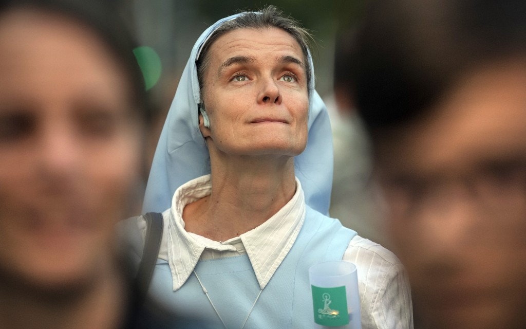 A nun holds a candle during a procession joined by tens of thousands in Budapest, Hungary, Saturday, Sept. 11, 2021, the day before the final mass of ...