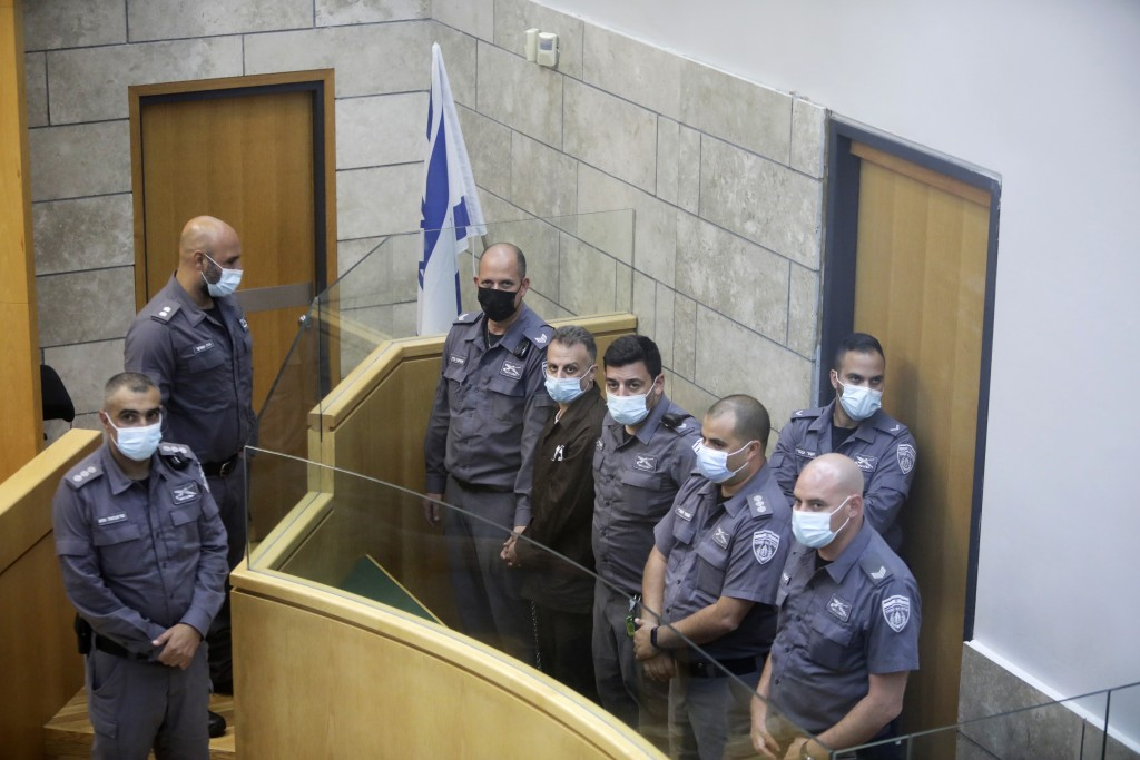 Yakub Kadari is surrounded by guards as they stand in a courtroom in Nazareth, Israel, after he and three other Palestinian fugitives were captured on...