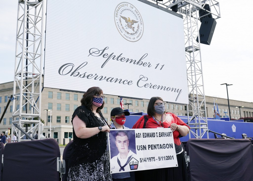 April Horton, left, Blake Edward Schaffer, 10, and Andrea Stauter, right, sisters and nephew of Petty Officer First Class Edward Earhart, who was kill...