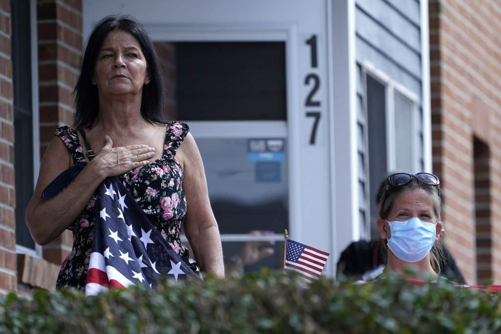 Residents watch the funeral procession for Sgt. Johanny Rosario Pichardo, a U.S. Marine who was among 13 service members killed in a suicide bombing i...