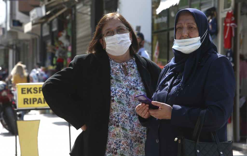 Two women look on as people march in silence to honor the victims in the burned out makeshift hospital in North Macedonia's northwestern town of Tetov...