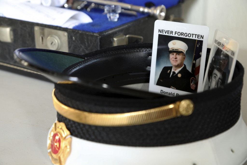 The photos of two firefighters killed at the World Trade Center sit in the hat of Assistant Chief John Pristas of the Cranberry Township Volunteer Fir...