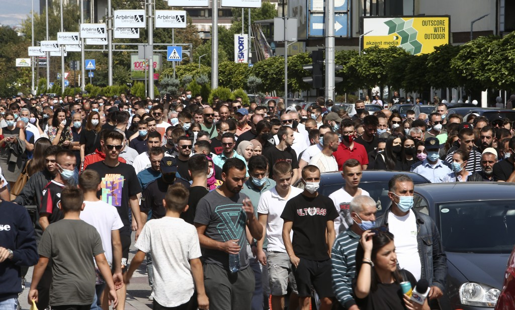 People march in silence to honor the victims in the burned out makeshift hospital in North Macedonia's northwestern town of Tetovo, Saturday, Sept. 11...