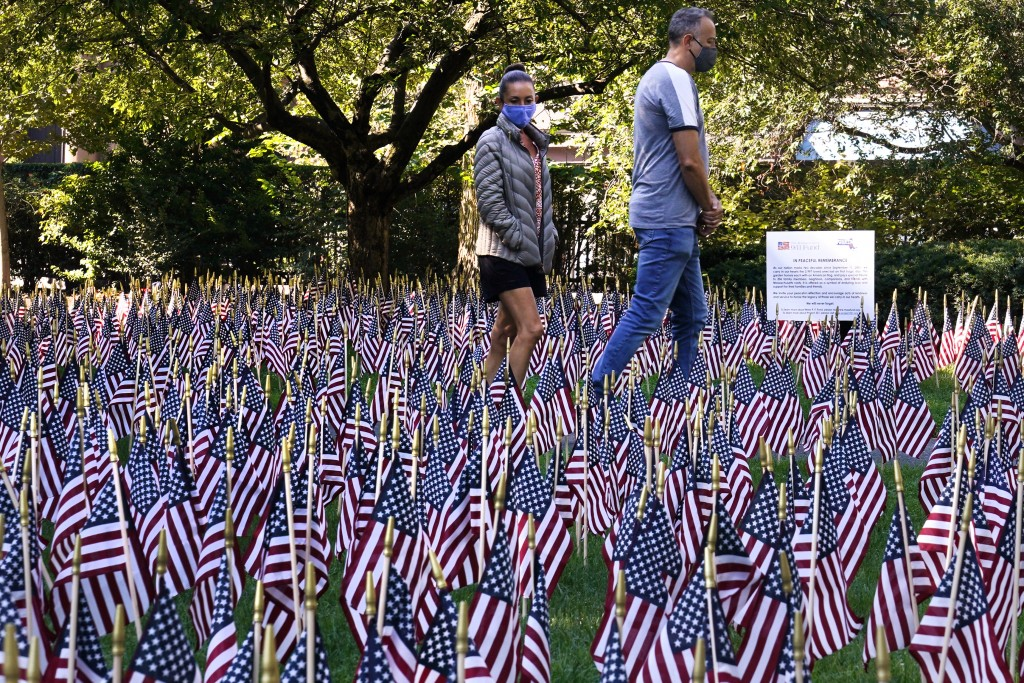 A couple, wearing protective masks due to the COVID-19 virus outbreak, walk along a path through nearly 3,000 flags, each representing a victim lost o...