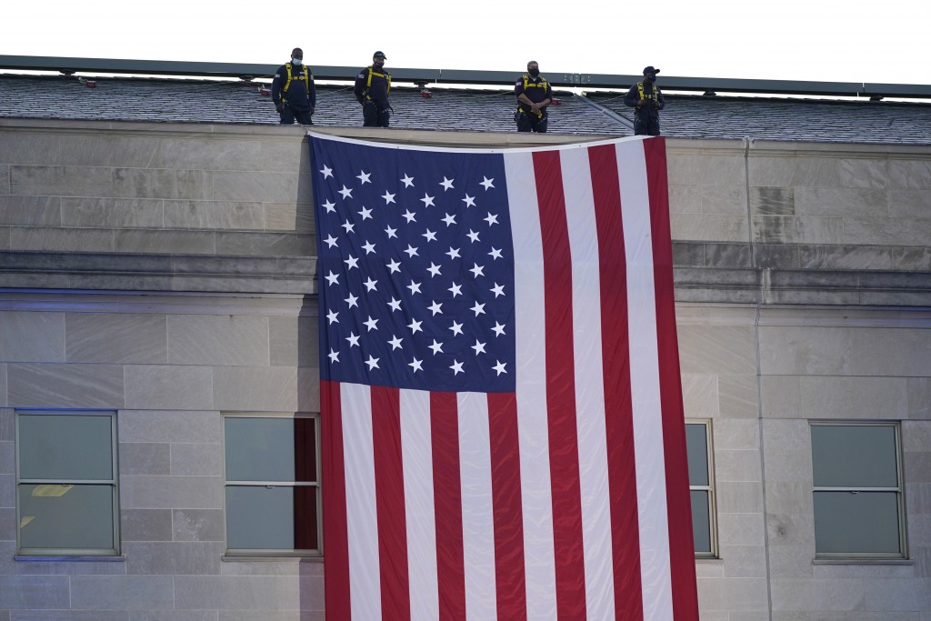 An American flag is unfurled at the Pentagon in Washington, Saturday, Sept. 11, 2021, at sunrise on the morning of the 20th anniversary of the terrori...