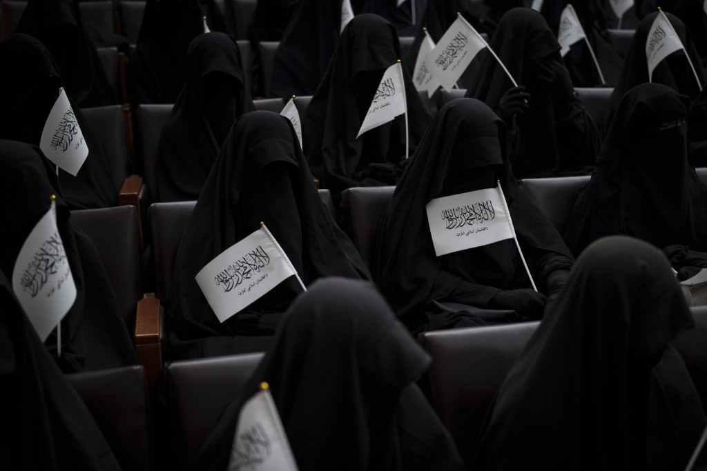 Women wave Taliban flags as they sit inside an auditorium at Kabul University's education center during a demonstration in support of the Taliban gove...