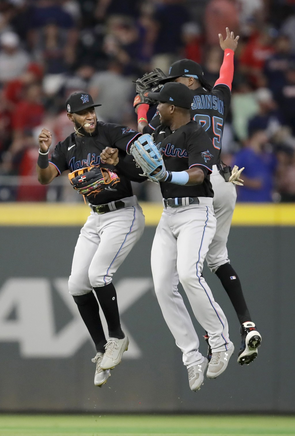 Miami Marlins outfielders, from left, Bryan De La Cruz, Jesus Sanchez, and Lewis Brinson (25) celebrate the 6-4 win over the Atlanta Braves at the end...