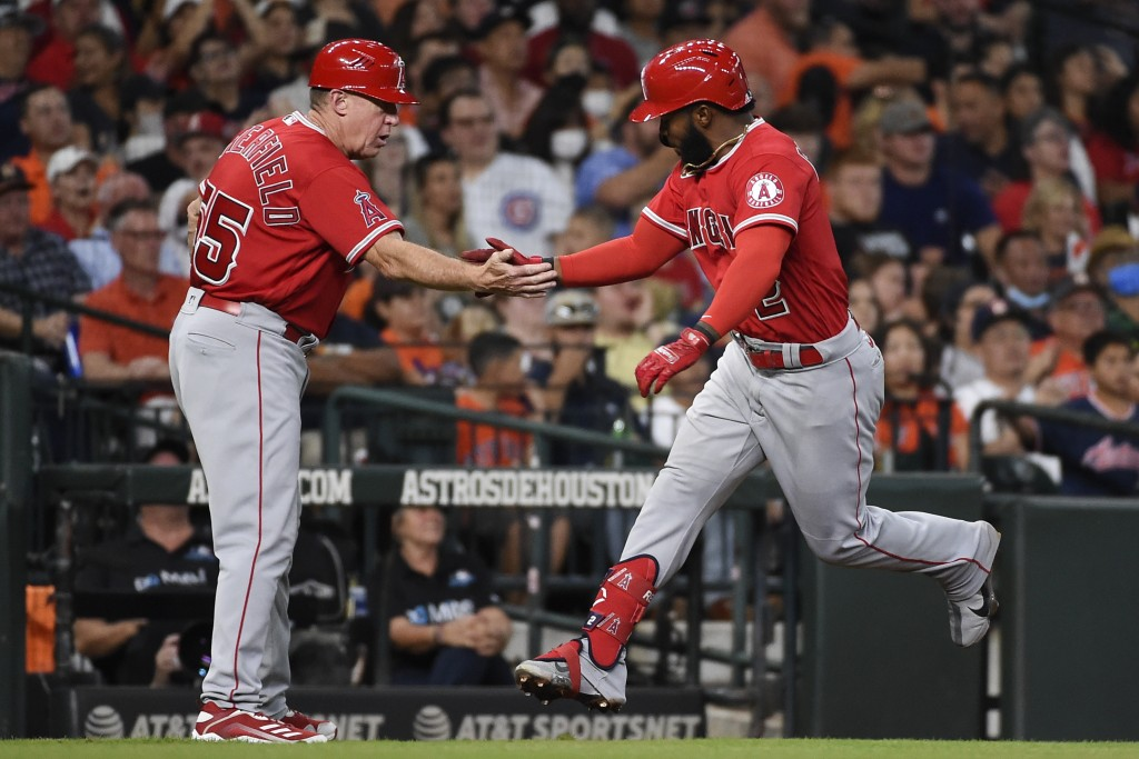Los Angeles Angels' Luis Rengifo celebrates his two-run home run with third base coach Brian Butterfield during the third inning of a baseball game ag...