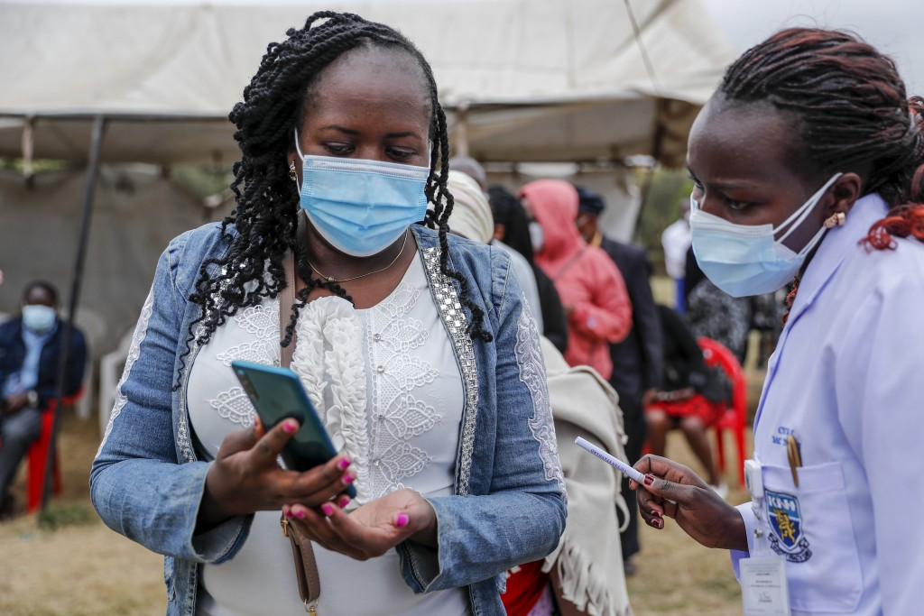 A woman uses her mobile phone to show to nurses the confirmation text message received that proves she has registered to receive the AstraZeneca coron...