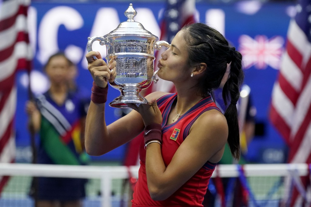 Emma Raducanu, of Britain, kisses the US Open championship trophy after defeating Leylah Fernandez, of Canada, during the women's singles final of the...