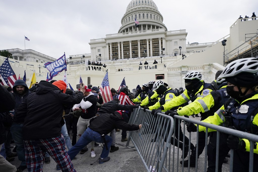 FILE - Trump supporters try to break through a police barrier, Wednesday, Jan. 6, 2021, at the Capitol in Washington. The U.S. Capitol Police said Sat...