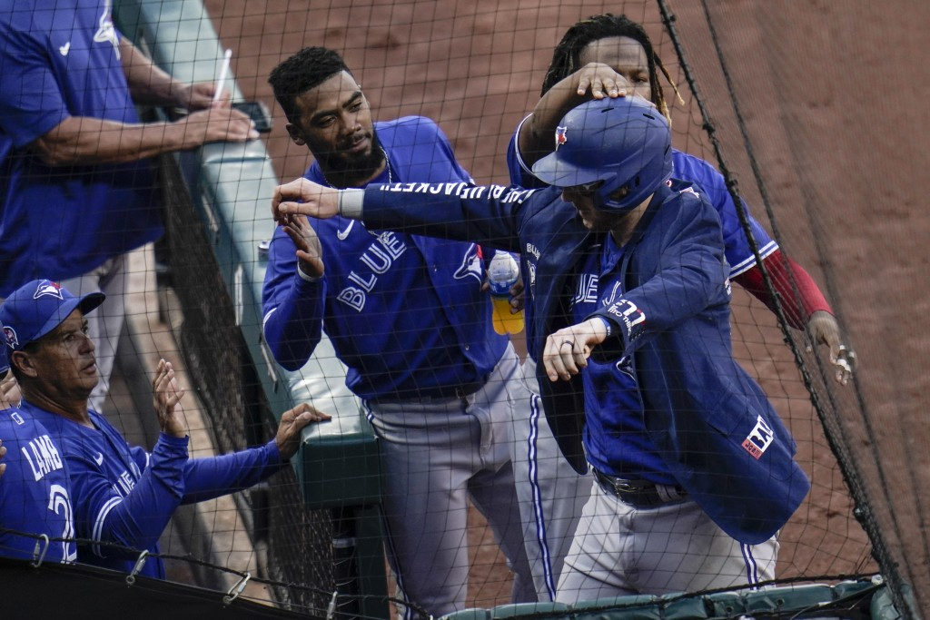 Toronto Blue Jays' Danny Jansen, front right, is greeted by teammates after hitting a two-run home run against the Baltimore Orioles during the fourth...