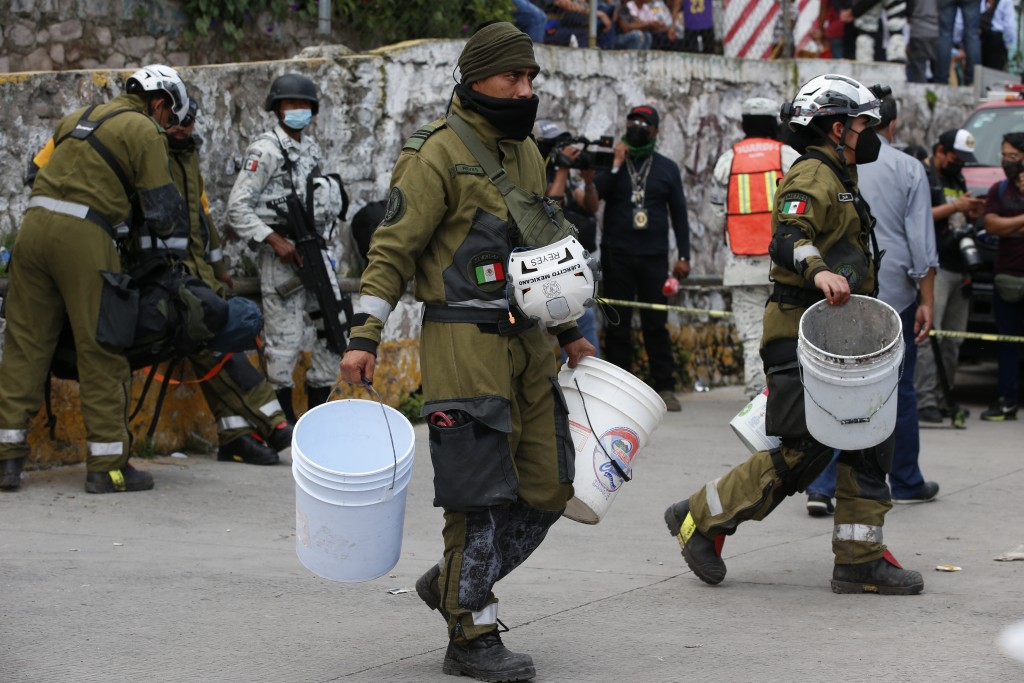 Soldiers carry buckets as they help in the search and rescue efforts at the site of a landslide that brought tons of massive boulders down on a steep ...