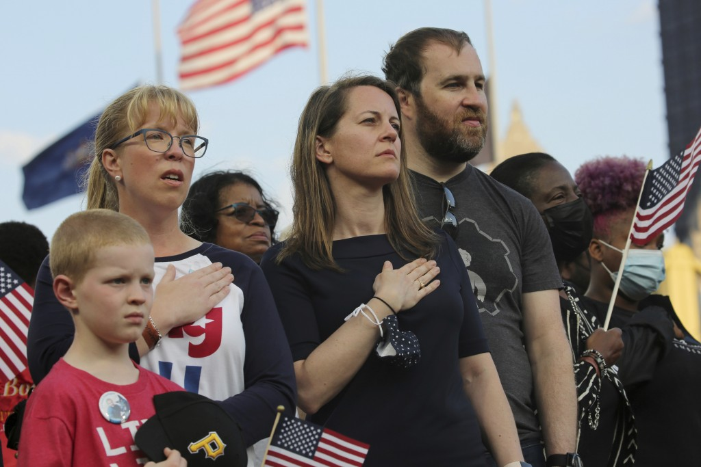 Relatives of those killed on Flight 93 stand as a large flag is unfurled on the field before the Pittsburgh Pirates take on the Washington Nationals i...